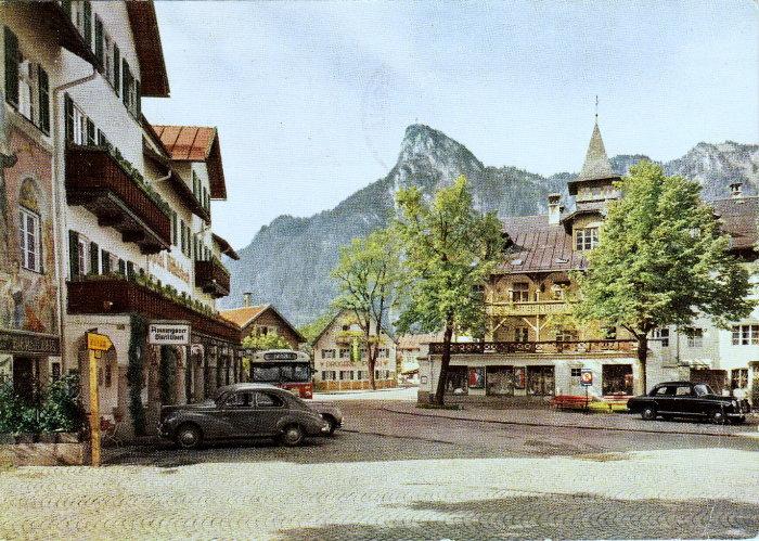 """""""Oberammergau - Dorfplatz mit Kofel"""": rechts im Bild vermutlich die beiden (in Rot gestrichenen) Bänke, von denen im Brief die Rede ist."""