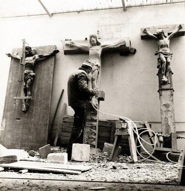 Berthold Rumold 1984 bei der Arbeit an einem Feldkreuz aus Sandstein. Rechts und links sieht man die Vorlagen, an denen er sich orientierte, ohne sie zu kopieren.